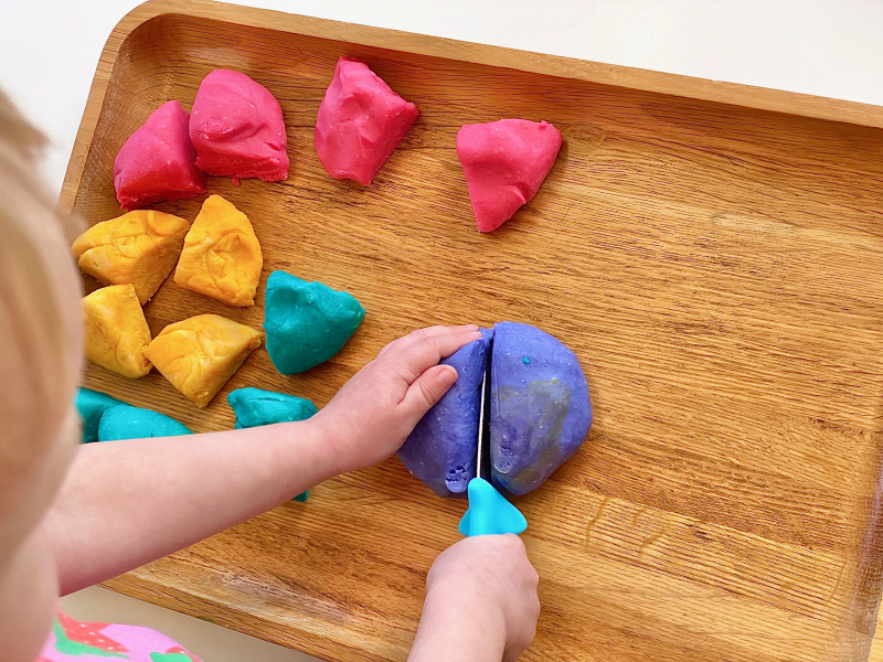 Cutting play dough into quarters at How we Montessori three years